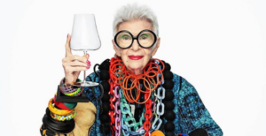 An old women, Iris Apfel is holding a wineglass