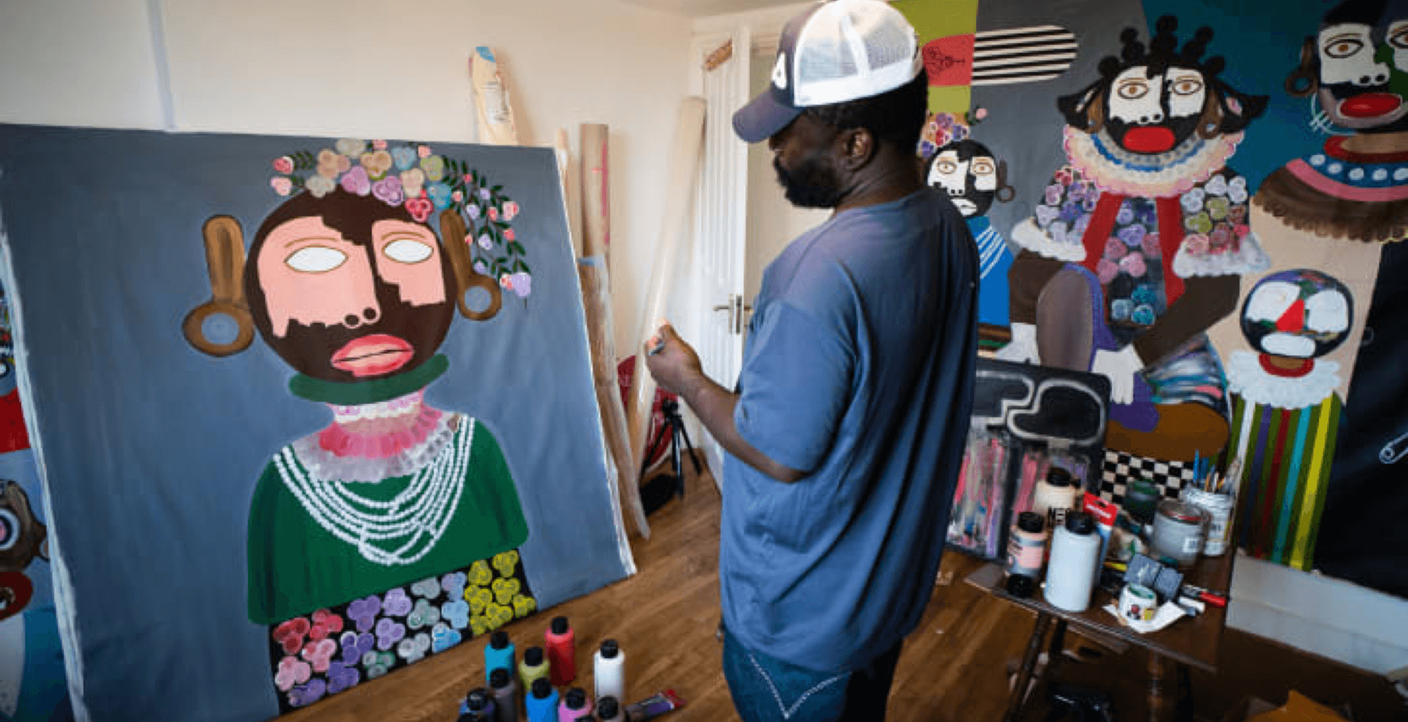 a guy, kojo marfo, is standing infront of an unfinished art work