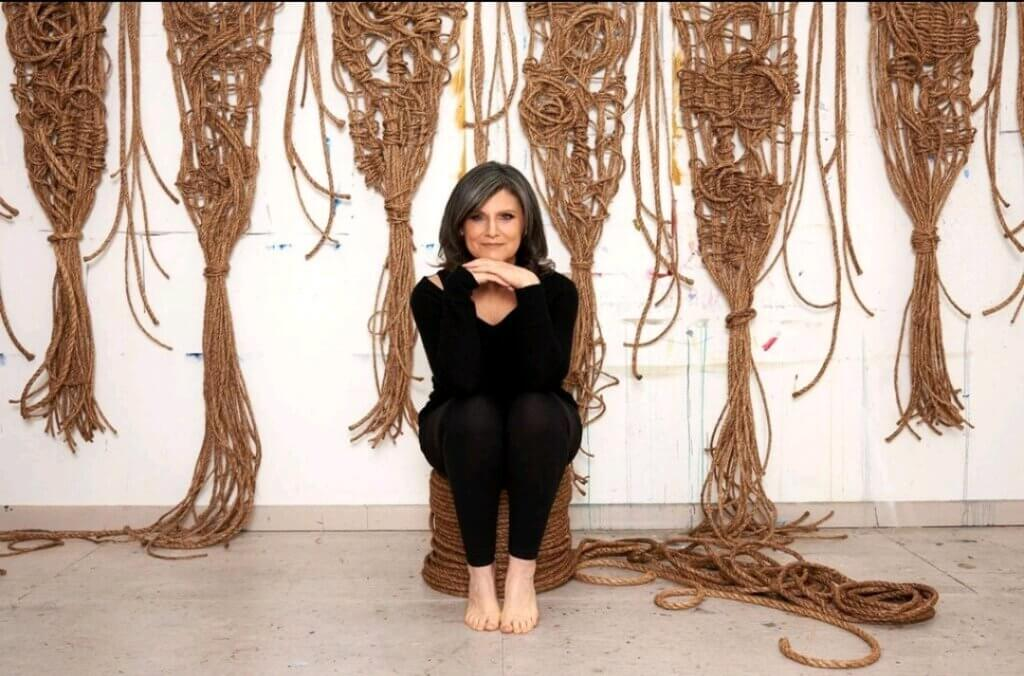 A women, Susan beallor Snyder, sits on a pile of rope, in the background are hanging six artworks of hers