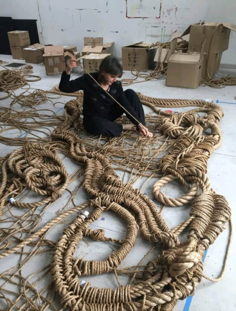 A women, Susan Beallor-Snyder is working on an artpiece, made out of heavy strings