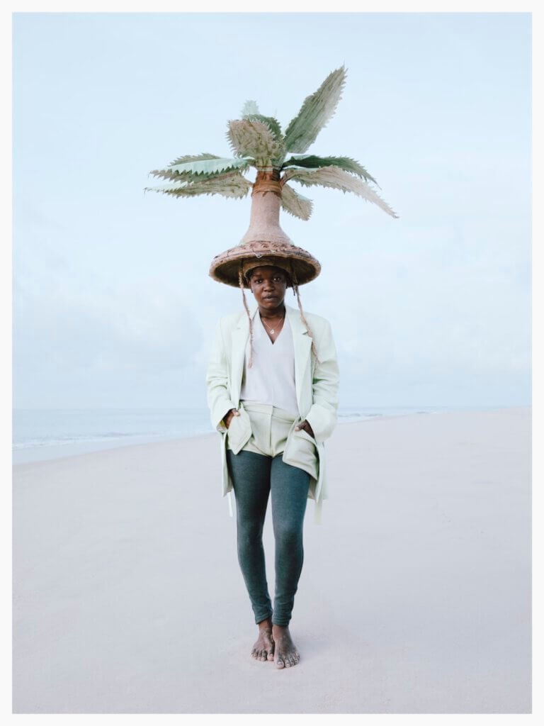 women standing on a white beach, the ocean and the sky in the background are also very light-coloured. she is waring a big head that looks like a palmtree