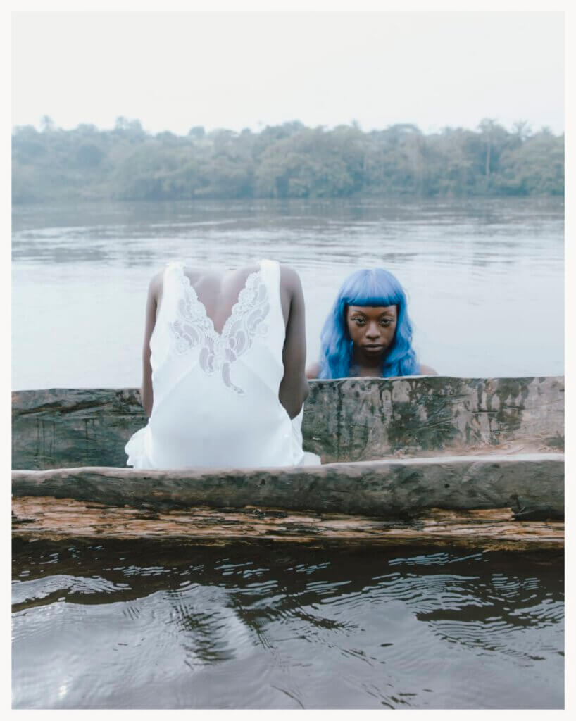a body in a white dress sits headless on a boat. Next to it there is a womens head with long blue hair. she is looking directly into the camera