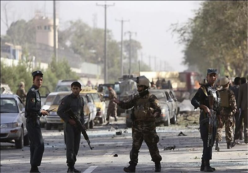 four men with weapons are standing on a chaotic street