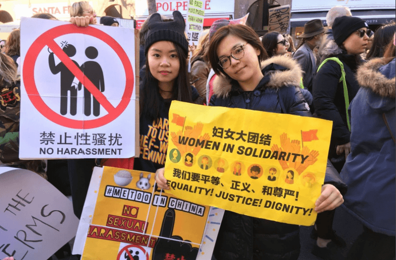 two women holding feminist posters