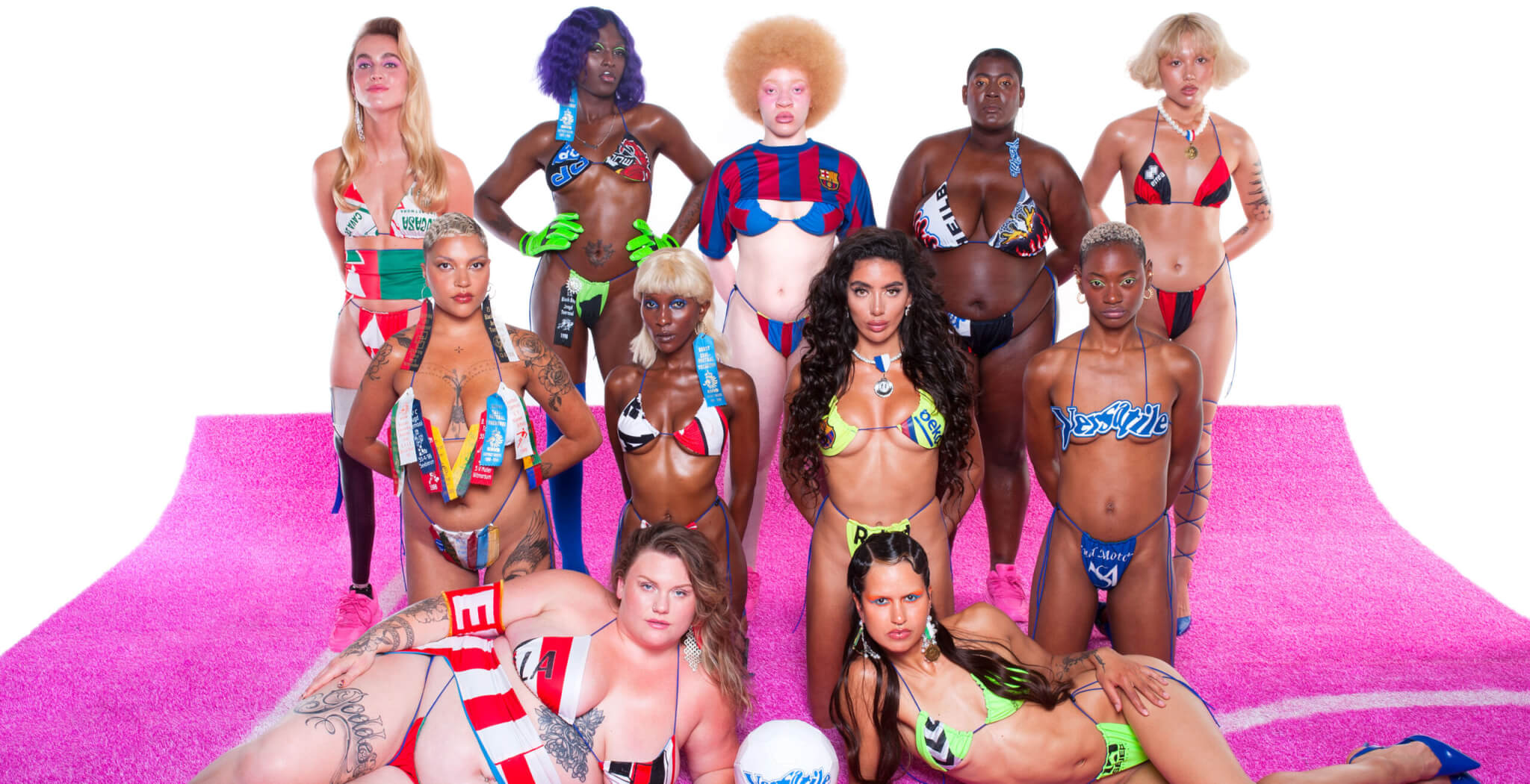 eleven women, wearing bikinis from Versatile Forever, are posing for a group foto on a pink soccerfield